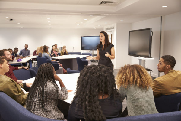 Female trainer addressing trainees in a classroom