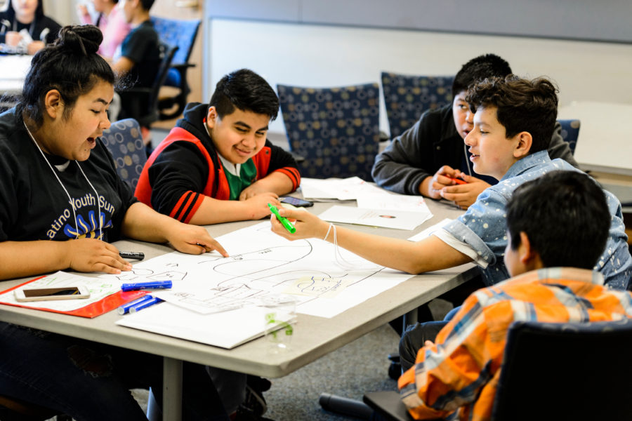 Latino middle schoolers work on a project together