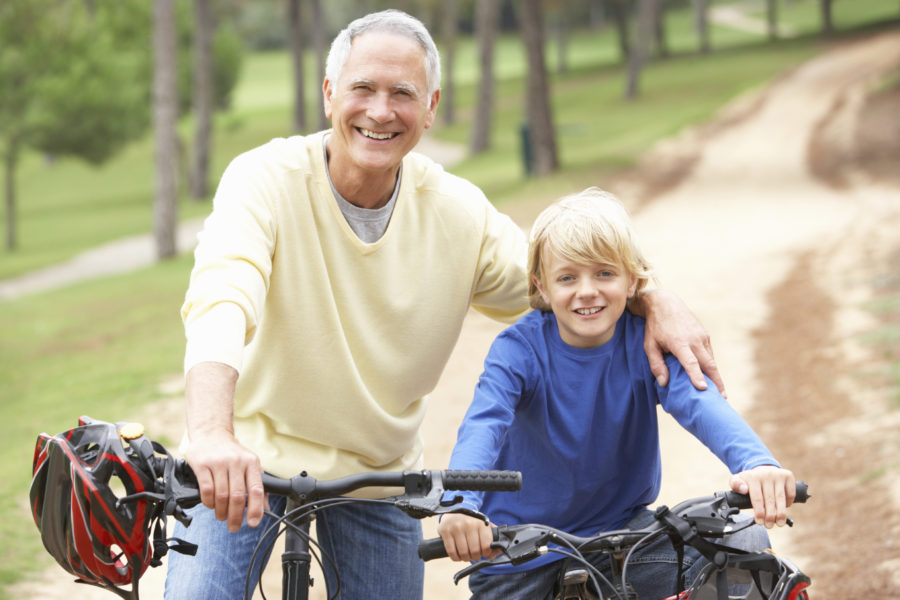 Grandfather biking with grandchild
